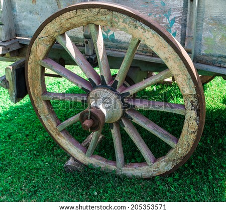 Old exhibit with the wagon wheel on a green grass - stock photo