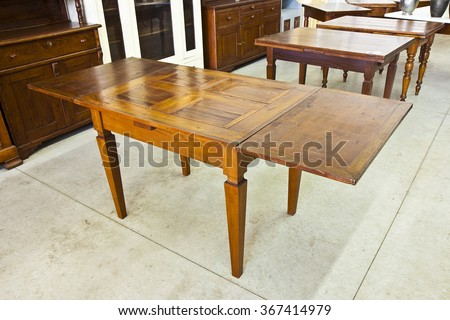 Old extensible italian wooden table just restored in a junk shop - stock photo