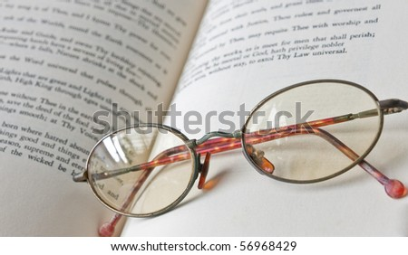 Old eyeglass on the book - stock photo
