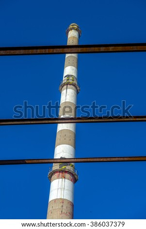 Old factory chimney. Clear blue sky in the background. - stock photo