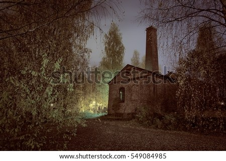 Old factory ruins in the middle of the spooky forest at night.