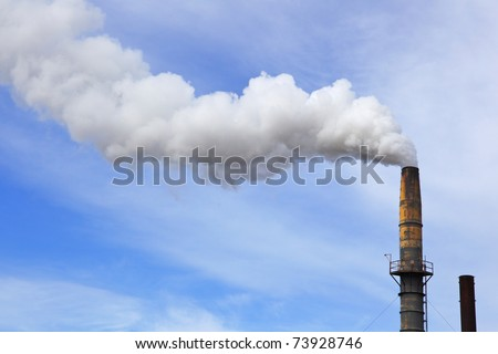 Old factory smoke stack billowing a white gray plume across blue and white cloud sky