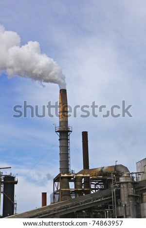Old factory smoke stack billowing a white gray plume across blue and white cloud sky - stock photo