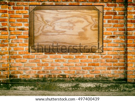 Old faded grunge wall of bricks texture or background with board for text