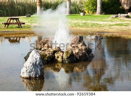 Old Faithful Geyser of California just starting a new eruption with steam and a small splash of hot water. - stock photo