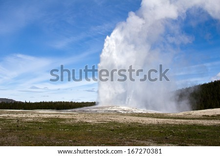 Old Faithful Geyser the iconic geyser in Yellowstone National Parks geothermal areas.  - stock photo