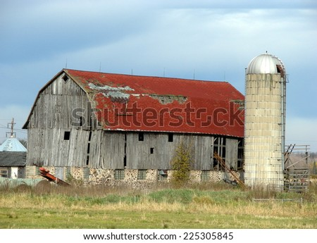 old farm building rural agriculture red barn roof silo gray barn - stock photo