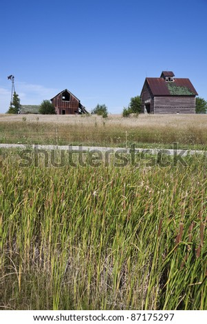 Old farm buildings in the middle of field - typical Midwest panorama - stock photo
