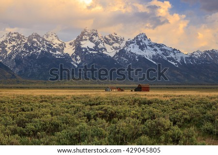 Old farm in a vast field with the Teton Mountains, Wyoming, USA. - stock photo