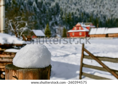 Old farm in the mountains at winter. focus on foreground snow of the fence.  Ukraine Carpathians - stock photo
