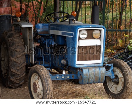 old farm tractor with mud on wheels in the shed