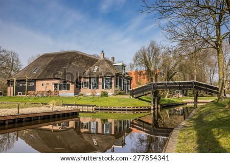 Old farm with reflection in the water in Giethoorn, Netherlands - stock photo