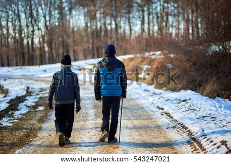 Old farmer and his grandson having a walk in a winter day in the countryside