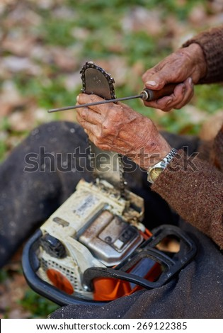 Old farmer doing maintenance work to his chainsaw - stock photo