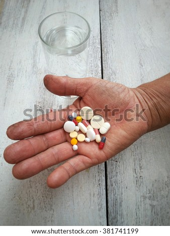 Old farmer hand holding medicine with glass of water.  healthcare and medical concept in vintage tone - stock photo