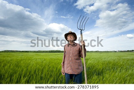 Old farmer with hayfork standing in green barley field in spring - stock photo