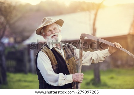 Old farmer with scythe taking a break from mowing the grass - stock photo