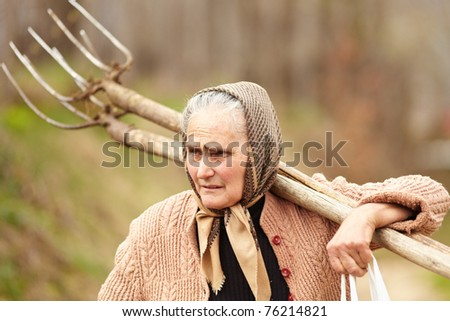 Old farmer woman carrying a fork, outdoor - stock photo