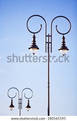 Old fashion decorative lamp post on the background of blue sky - stock photo