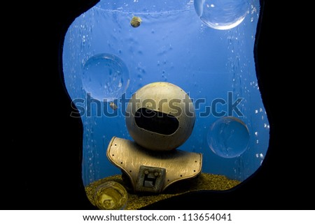 Old fashion diving helmet submerged in the water. - stock photo