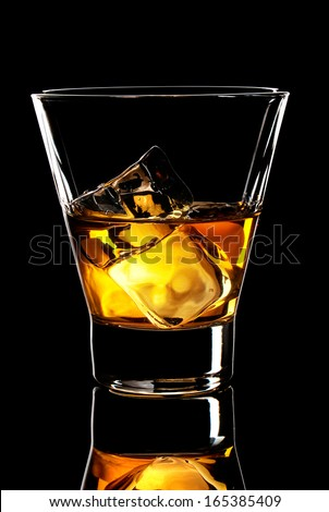 old fashion glass of whiskey with ice cubes on a black background