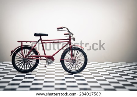 Old Fashion hand made model bcycle on a white background and checked floor. - stock photo