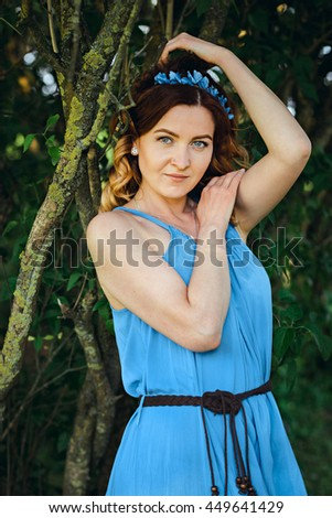 Old fashion portrait of a beautiful elegant red-haired woman dressed in a blue dress and a wreath of flowers posing in a windy Sunny day in a summer outfit, in nature. European city - stock photo