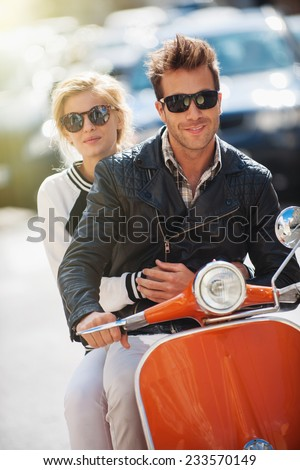 old fashionable couple riding  a vintage scooter in the street, man wears leather jacket and woman has a topknot and sunglasses - stock photo