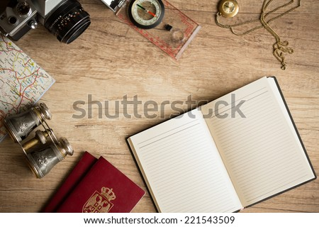 Old fashionable travel stuff on wooden table - stock photo