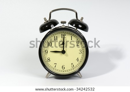Old fashioned alarm clock showing 9 o'clock on a white background
