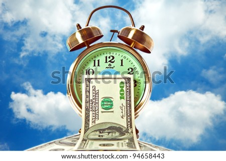 Old fashioned alarm clock with stack of 100 dollar bills on sky background - stock photo