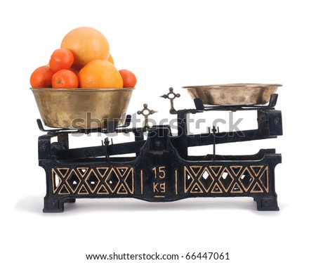 Old-fashioned balance scale with citrus isolated  on white background - stock photo
