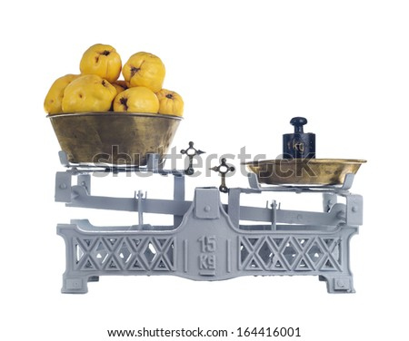 Old-fashioned balance scale with quinces isolated on white background - stock photo