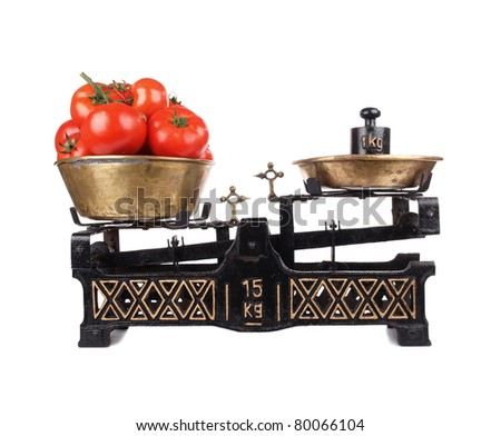 Old-fashioned balance scale with tomatoes isolated on white background - stock photo