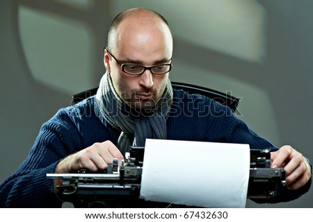 Old fashioned bald writer in glasses writing book on a vintage typewriter - stock photo