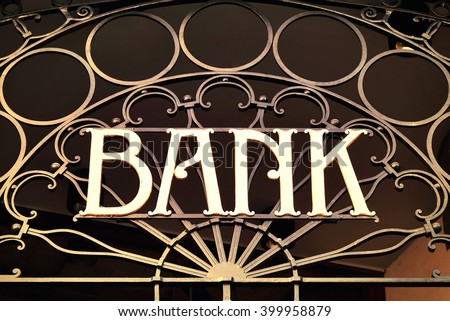 Old fashioned bank sign with ornamental wrought iron and golden letters. Building exterior of a bank. Finance symbol.  - stock photo