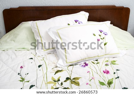 Old fashioned bed with floral bedding - stock photo