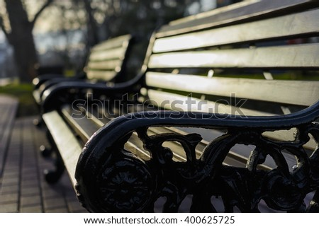 old fashioned bench in the spring park in the morning - stock photo
