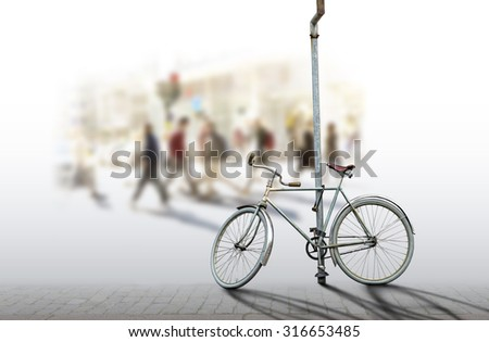 Old fashioned bicycle attached with lock to pole with people in city in background - stock photo