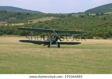 Old-fashioned biplane landed. A vintage camouflage biplane secured to the ground at a grassy airfield.  - stock photo
