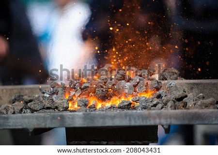 Old fashioned blacksmith furnace with burning coals - stock photo