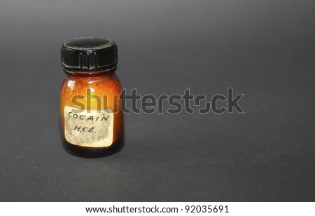 Old fashioned bottle with cocaine on black - stock photo