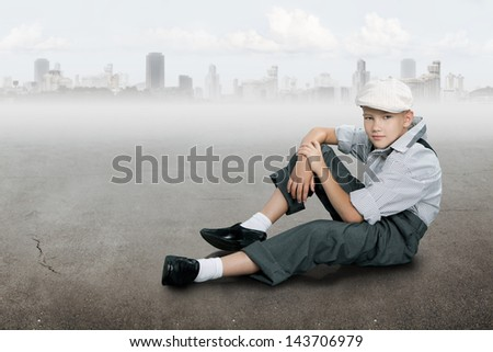 Old fashioned boy looking to the camera and sitting on a ground near city - stock photo