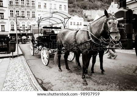 old fashioned carriage with horses in sepia - stock photo