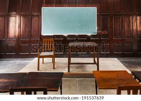 Old fashioned classroom with wood paneled walls and blank chalk board. - stock photo