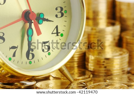 Old-fashioned clock dial on golden coins background, time is money concept