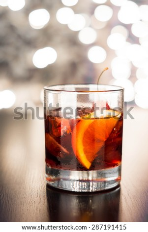 Old fashioned cocktail on the bar table with bokeh background. Toned image in sepia style. - stock photo