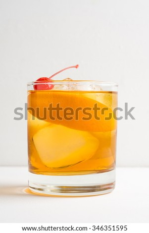Old fashioned cocktail with cherry and orange peel - stock photo