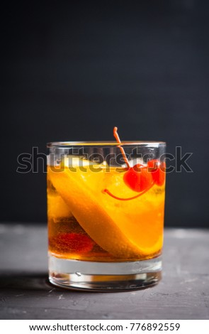 Old fashioned cocktail with cherry and orange. Selective focus. Shallow depth of field.