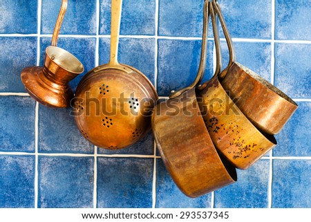 Old fashioned copper kitchenware, utensils. Hang on iron hooks against blue tile wall. Coffee maker, colander,  antique pans: casserole, stewpot, pot. - stock photo